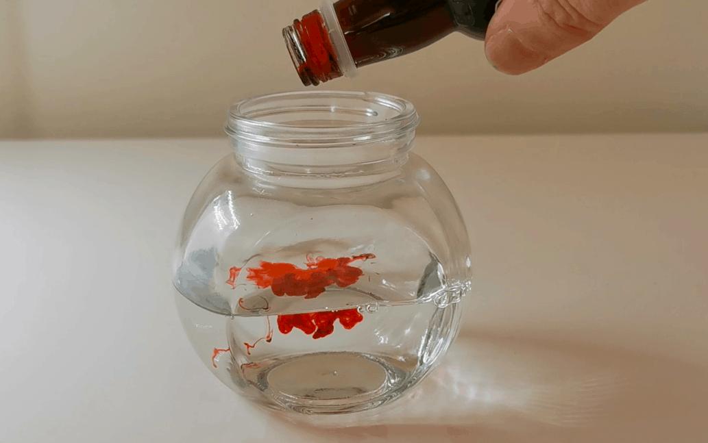 Adding red liquid color in sensory jar