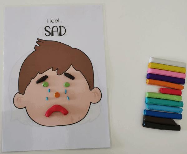 Playdough Mat with a sad Face and assorted playdough colors